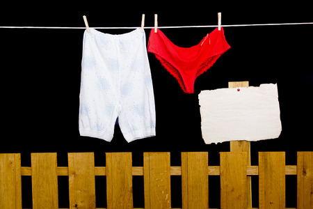 dry cleaned: Womens pants hanging on a rope over the fence