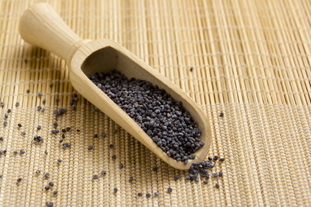 poppy seeds: Poppy seeds in a wooden spoon on a straw napkin