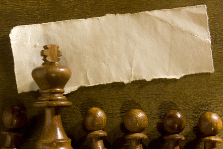 shred: Chess figure and shred paper on dark wooden background Stock Photo