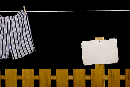 dry cleaned: Men�s underwear hanging on a clothesline over the fence Stock Photo