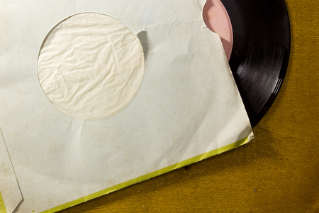 turn table: Vintage gramophone vinyl record in an envelope on wooden backgro Stock Photo