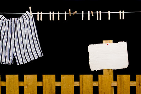 dry cleaned: Men's underwear hanging on a clothesline over the fence Stock Photo