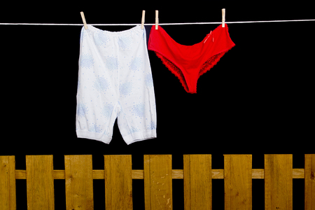 dry cleaner: Womens pants hanging on a rope over the fence