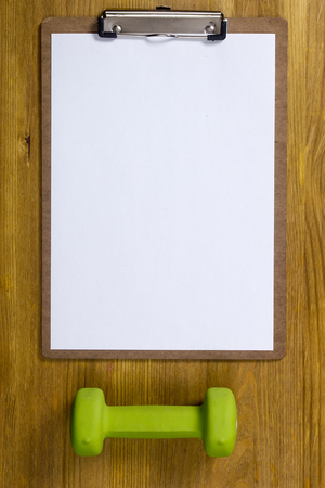 write a letter: Set of paper and dumbell on a wooden table