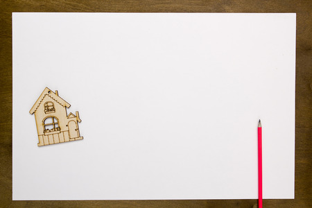 repossession: Model home on a white sheet of paper on a wooden table Stock Photo