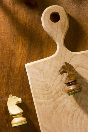 Chess pieces and cutting board on a wooden background Stock fotó