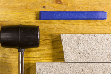 chisel: Rubber hammer and chisel on a background of stone cladding Stock Photo