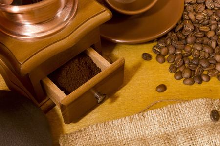 Coffee beans and grinder on wooden table