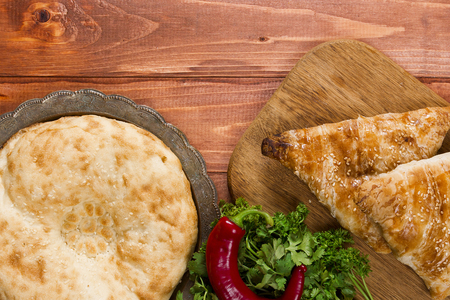 non: Traditional Uzbek bread and samosas on wooden background Stock Photo