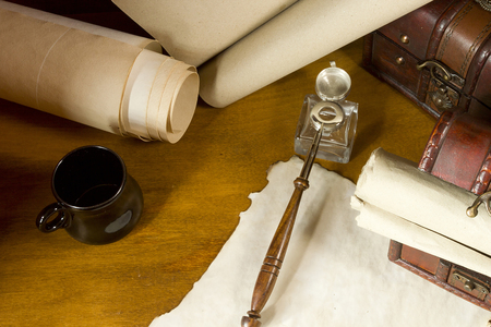 pluma de escribir antigua: Vintage scrolls and tools for writing in ink on a wooden table Foto de archivo