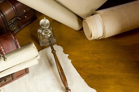 pluma de escribir antigua: rollos de �poca y herramientas para escribir con tinta en una mesa de madera Foto de archivo
