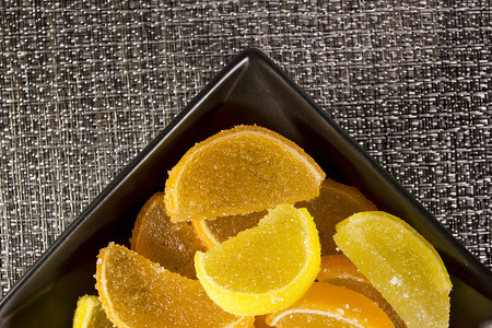 jellybean: Candy jujube as lemon and orange slices in a black ceramic ware