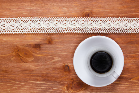 Openwork lace on the wooden surface and a cup of coffee. Stock Photo
