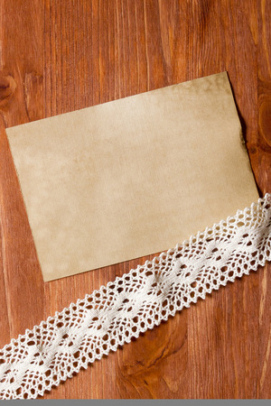 skillfully: Openwork lace on the wooden surface, and old paper.