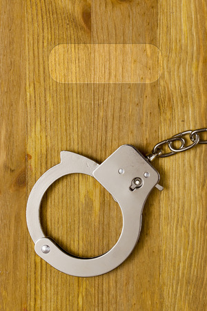 Tool restriction of freedom - the handcuffs. Handcuffs on a wooden surface. Reklamní fotografie