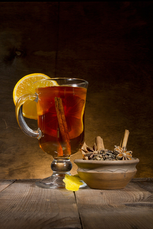 Mulled wine and set of spices on a wooden background