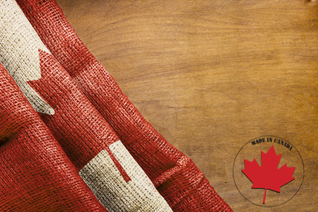 canada stamp: Flag of Canada on a wooden background and the label Made in Canada.