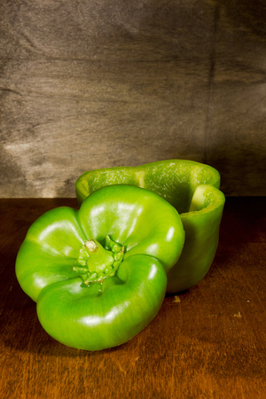 Green bell peppers ready to be stuffed on a wooden table