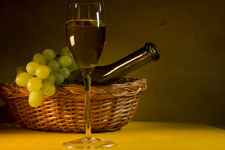 Bottle and glass of white wine and a bunch of grapes. Stock Photo
