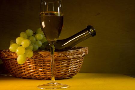 vaso de precipitado: Bottle and glass of white wine and a bunch of grapes. Foto de archivo