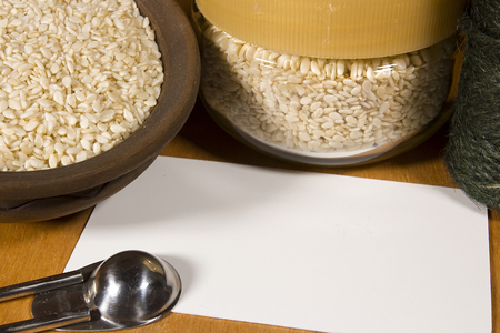 Sesame seeds in different containers with packing cord