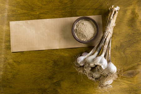 Heads of garlic in the beam and ground on a wooden table