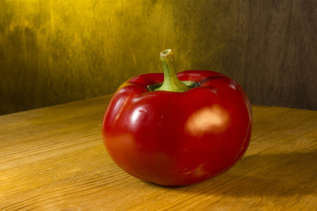 Ripe red pepper on a wooden background