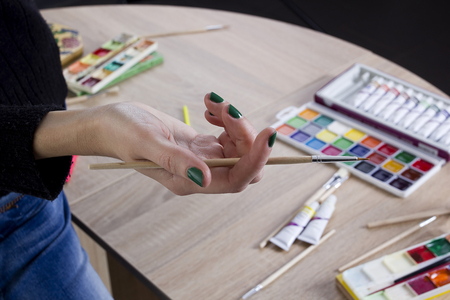 The artist's hand drawing a paint, brushes and pencils. Art background Stock fotó