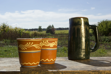 Stein and clay cups on the background of the rural landscape Stock Photo
