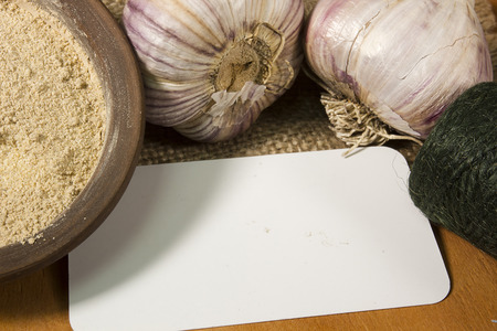 Heads of garlic and garlic powder to the coil of rope and card Imagens