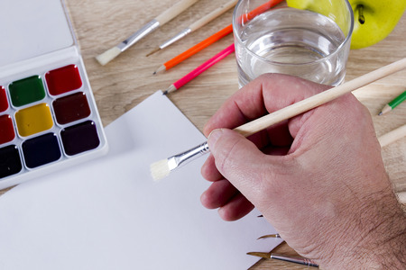 The artist's hand drawing a paint, brushes and pencils. Art background photo