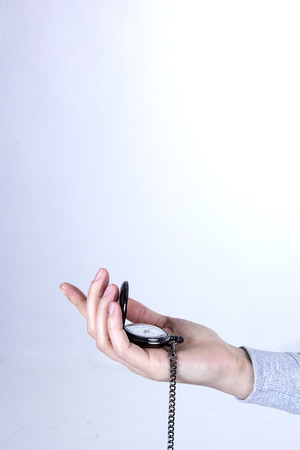Pocket watch in a female hand on a white background