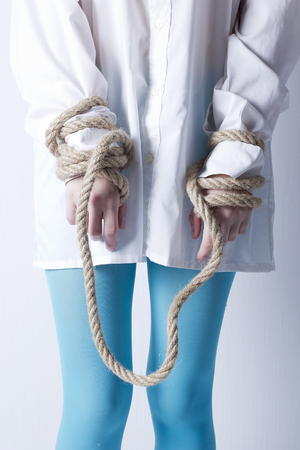 girl tied: Crazy kind of young girl with hands tied with rope Stock Photo