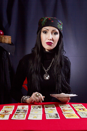 Sorceress wonders by Tarot cards on a black background Stock Photo