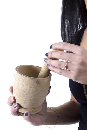 Wooden mortar in female hands on a white background