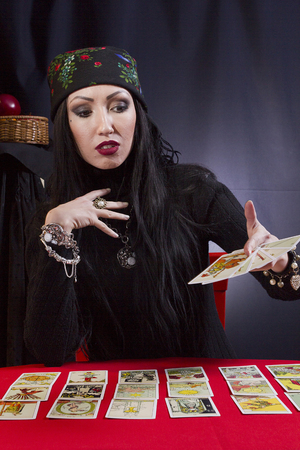 Gypsy woman wonders on the Tarot cards on a black background Stock Photo
