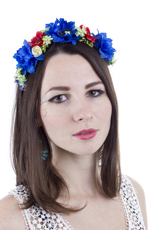 Portrait of a girl in a wreath of flowers on a white background