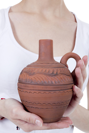 Clay pitcher in female hands on a white background