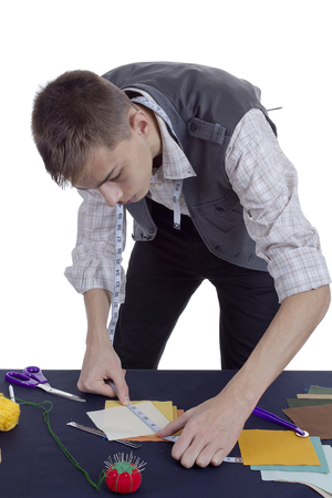 Young man tailor at work on white background Stock Photo