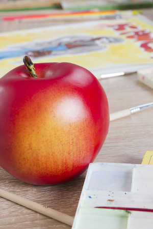 Red apple and pencils, paints and drawings
