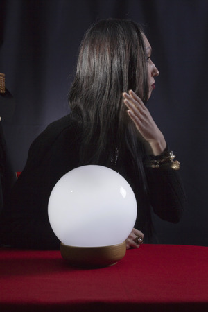 adivino: Fortune teller with a magic ball on a black background