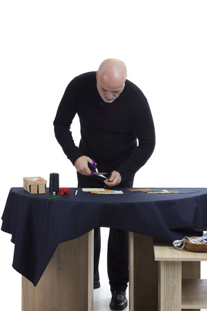 Mature tailor at work on a white background photo