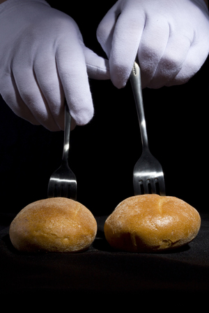 Buns on the forks and hands in white gloves on a black background