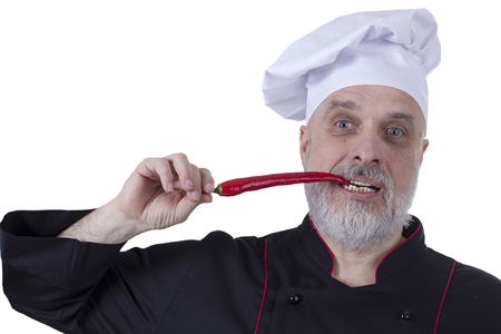 Bearded chef biting hot chili pepper on a white background photo