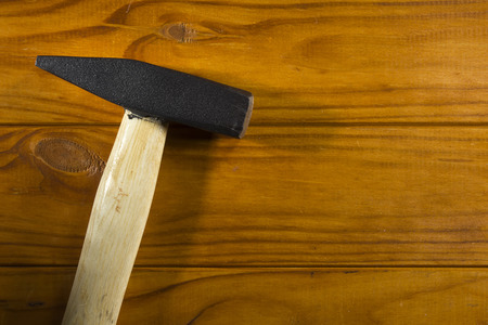 Hammer for hammering nails on the wooden background