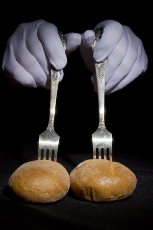 chaplin: Buns on the forks and hands in white gloves on a black background