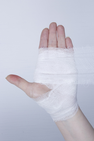 White medical dressing on a traumatized female hand