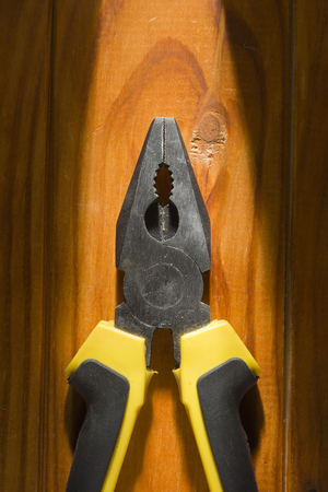 Close up of a multitool pliers on wooden background Archivio Fotografico