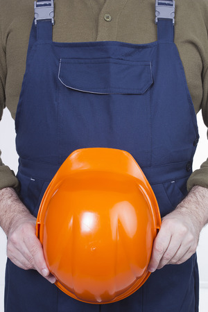 redecorating: Man in work clothes and with an orange protective helmet in hands Stock Photo