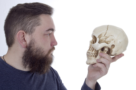 occultism: Bearded man with a human skull in his hand